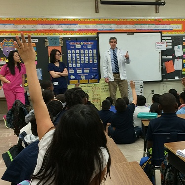 Doctor Jay and two dental team members presenting at Springhill Lake Elementary School