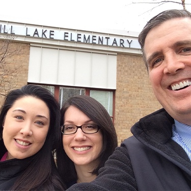 Doctor Jay McCarl and two dental team members outside of Springhill Lake Elementary School
