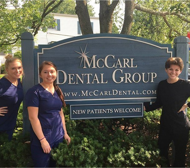 Team members by McCarl dental group sign