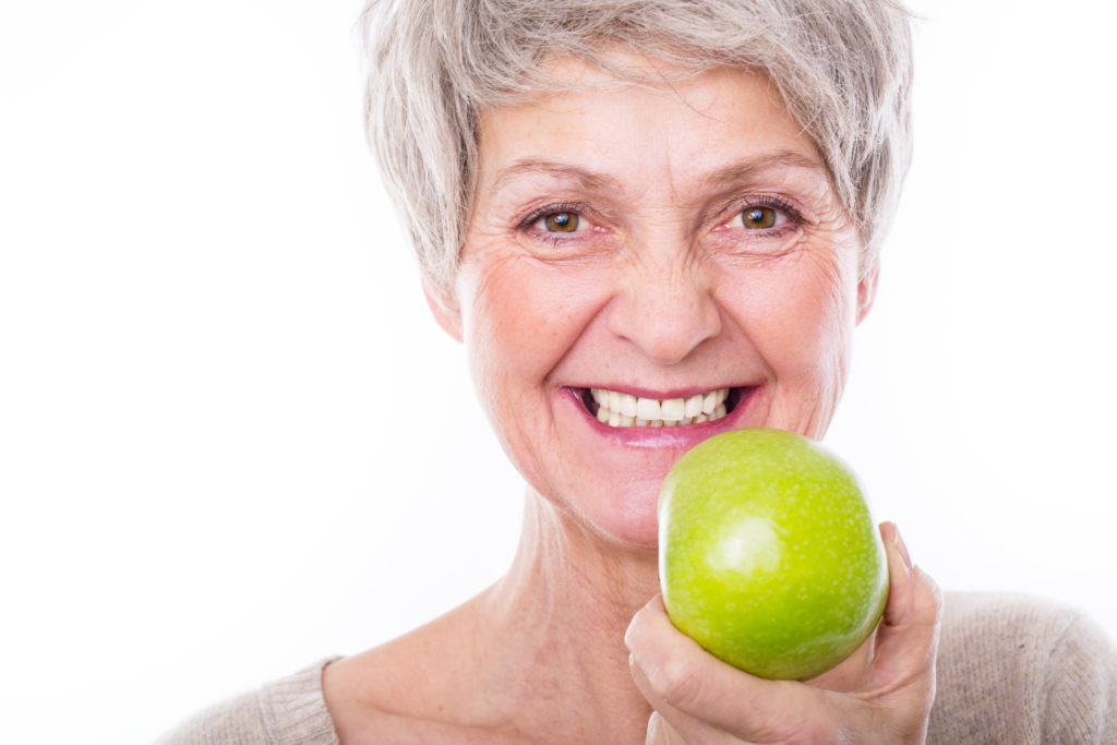 Smiling senior woman holding an apple
