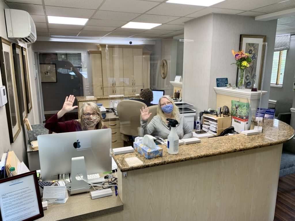 Two dental team members at front desk waring face masks